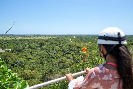 Young lady wearing a helmet enjoys a moment of rest from a sporting activity, admiring a tropical panoramic view from a height. Full sunlight, with orange flower and ocean at the horizon line. 版權商用圖片