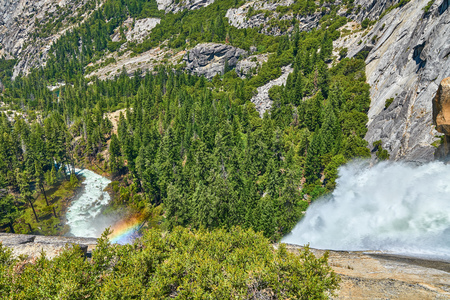 Vernal Falls in Yosemite National Park view from the top with rainbow rocks and valley