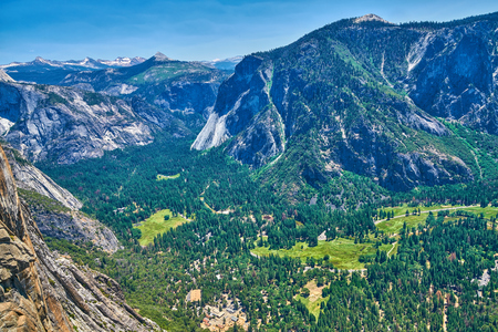 View of the Yosemite Valley with Visitor Center and the Sierra Nevada mountain range from the trail to Upper Yosemite Falls