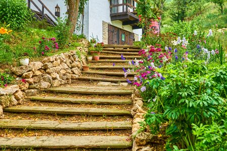 Old stairs footpath lined with flowers and rocks leading to house on a hill 版權商用圖片