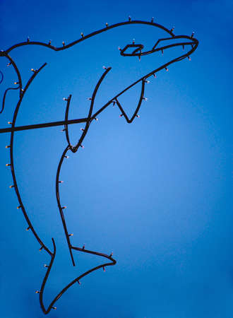 Wire Dolphin Lit Up with Blue Sky in background Stock Photo