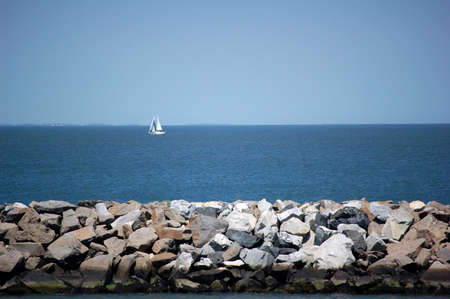 Sail Boat in background with rock wall in foreground