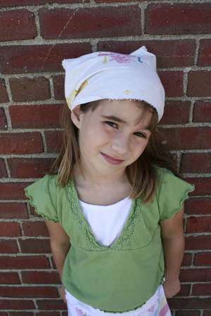 Little girl leaning against brick wall wearing green shirt and kerchief photo