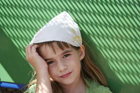 Sad little girl with green background wearing kerchief staring into camera Standard-Bild