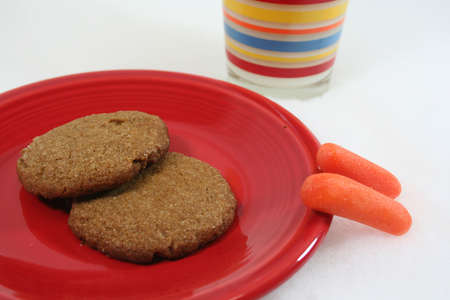Two cookies on red plate for Santa and two carrots for reindeer with glass of milk