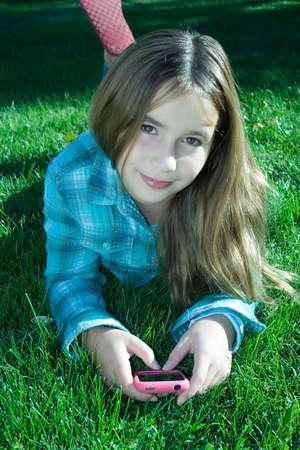 interakcje: Pretty young girl gospodarstwa telefon komórkowy zniesienia znajdujących się na trawę