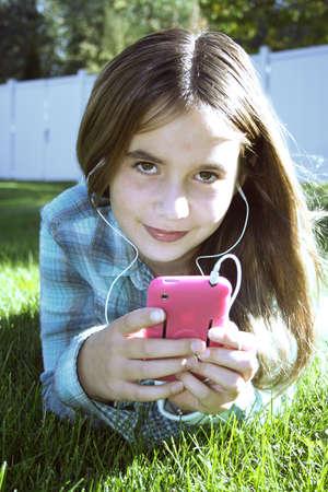 preadolescentes: Chica de interpolaci�n de colocaci�n en la hierba verde, escuchar m�sica en mp3 reproductor