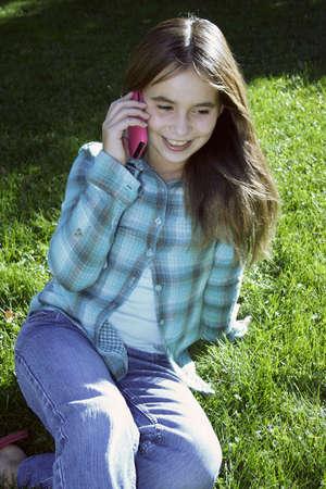preadolescentes: Ni�a sonriente, hablando por tel�fono celular sentado sobre c�sped