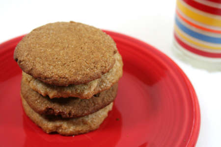 Stack of 4 cookies on red plate with glass of milk for Santa Banco de Imagens