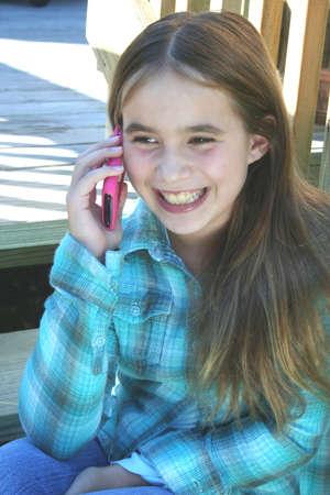 mobiele telefoons: Lachende pre-tiener meisje, praten op mobiele telefoon Stockfoto