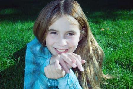 looking into camera: Sorridente pre teen girl esaminando la fotocamera
