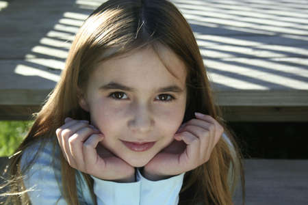 chin on hands: Pre teen girl sitting on steps with chin in hands