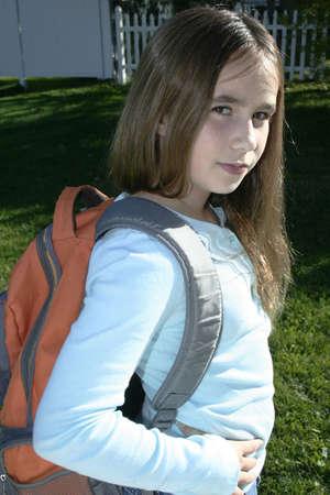 pre teen girl standing wearing back pack