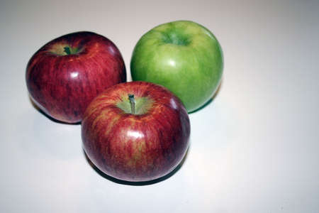 two red and one green apples on white background isolated Stock Photo