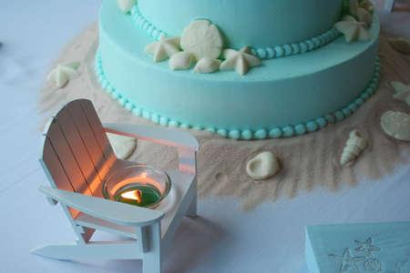 beach wedding: Beach themed aqua wedding cake with lit candle and candy shells