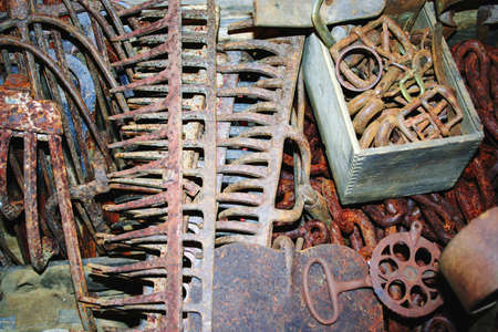 the hand tools: Assortment of rusted hand tools including rakes, pitchforks, and chain Stock Photo