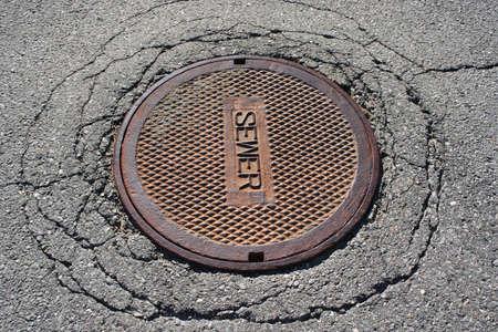 Rusted manhole sewer cover on cracked asphalt street