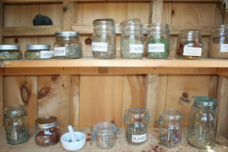 Dried herbs in bunches and jars for culinary and spa use photo