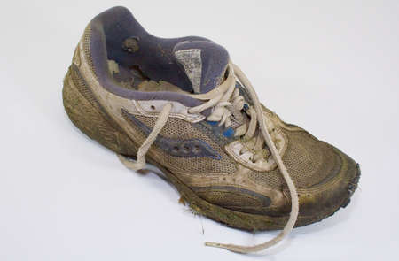 dirty feet: Dirty old grass stained lawn mower worn out sneaker