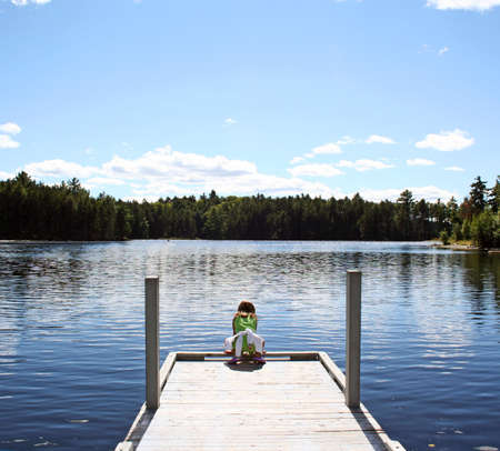 maine: Little girl on dock at lake in Maine Stock Photo