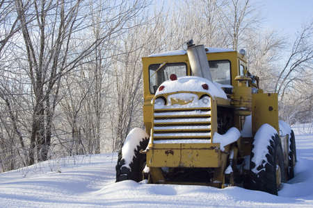 Snow covered tractor abandoned Standard-Bild
