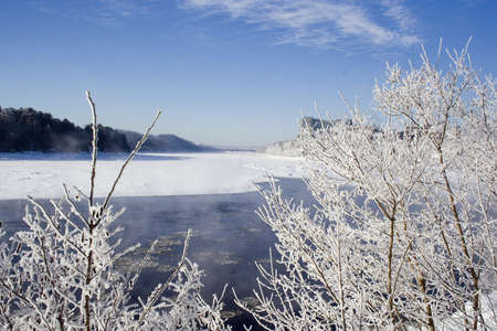 Winter scenic of frozen river and frosty branches