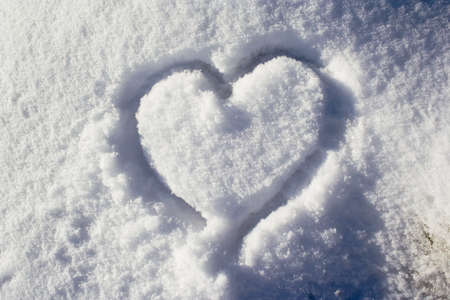 hearted: Heart shape in fresh white snow Stock Photo