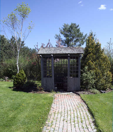 Garden shed with brick path leading in green grass photo