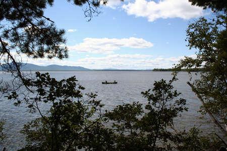 Summertime recreation paddling canoe on lake in Maine