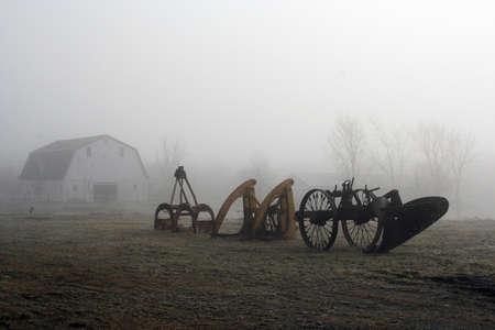 Old farm equipment and barn in foggy field