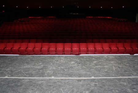 Red theater seats in small theater front row