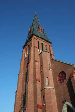 Tall catholic church steeple against blue sky