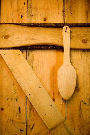 Rough wooden door with wooden spoon paddle hanging