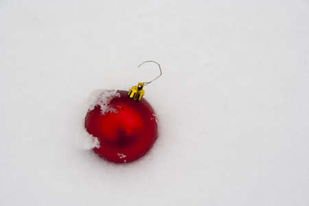 single red Christmas ornament in fresh new snow with snow detail