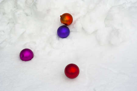 Colorful Christmas ornaments tossed into fresh snowfall