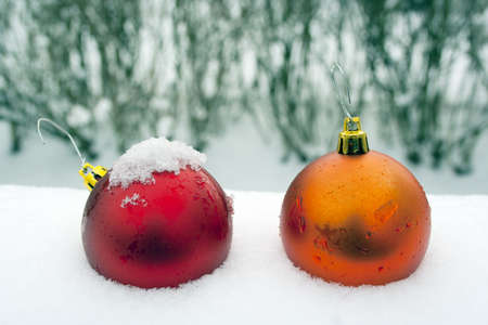 Red and orange Christmas ornaments in fresh snow with water droplet detail