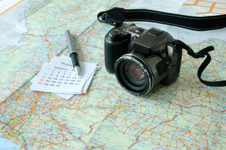 Camera, calendar and pen placed on map suit for holiday trip planning concept