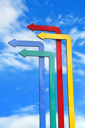 business direction: Colored arrows in blue sky background for successful business direction concept Stock Photo
