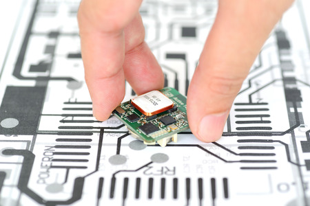 Closeup hand picking electronics device on schematics background