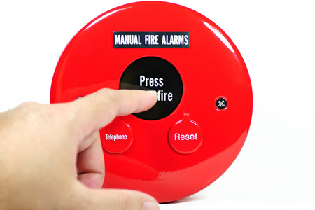 activate: Finger pressing on manual fire alarm button to activate the system
