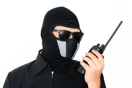hijack: Terrorist in black jacket with sunglass handle handheld radio walkietalktie