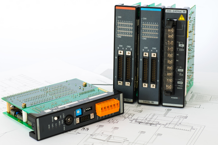 Isolated industrial PLC modules place on automatic process control diagram papers Foto de archivo