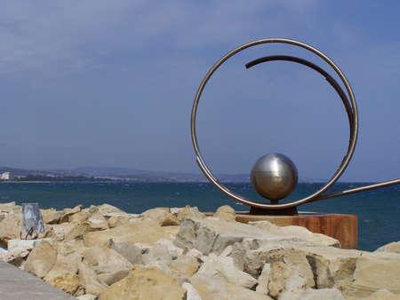 limassol: Steel sculpture with limassol in background. Stock Photo