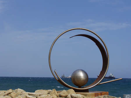 artful: Steel sculpture with ships in background in Cyprus.