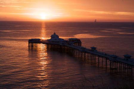 sunup: Sun-rising over Llandudno pier in North Wales.