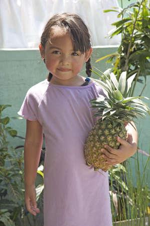 filipina: Pretty young pilipino girl holding a pineapple Stock Photo