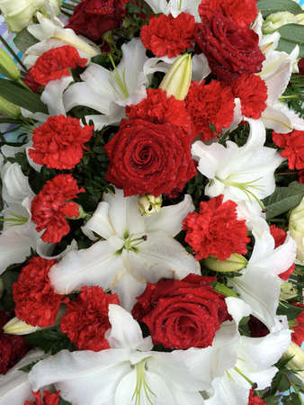 tribute: Floral tribute of red roses and carnations on a bed of lilies. With rain and dew drops on the petals.