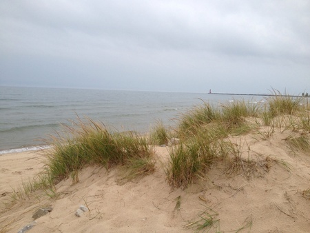 Lake Michigan with lighthouse and beach grass with a cloudy sky Stock Photo