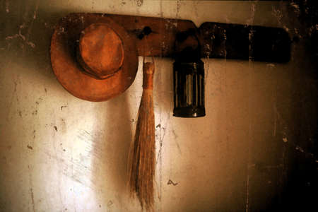 Retro Pin Rack in Farm House with Leather Hat Lamp and Grass Hand Broom photo
