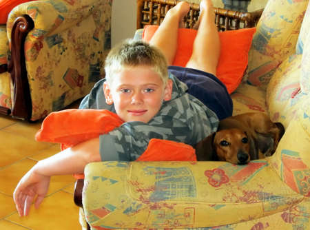 Boy and Pet Miniature Dachshund on Sofa  photo